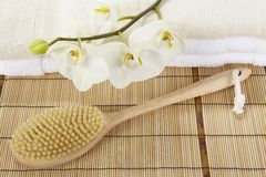 Bath brush on a bamboo mat, towels and a orchid Royalty Free Stock Photos