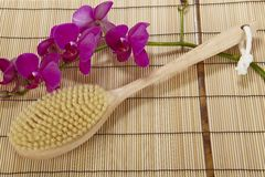 Bath brush on a mat of bamboo and an orchid Royalty Free Stock Image