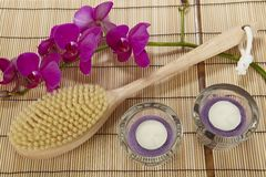 Bath brush, orchid and tealights on a mat of bamboo Stock Photography