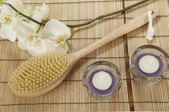 Bath brush, orchid and tealights on a mat of bamboo Stock Photos