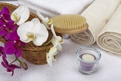 Bath brush, rolled towels, tealight and orchids Stock Photography