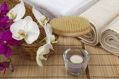 Bath brush, rolled towels, tealight and orchids. A bath brush with purple and white orchids into a basket standing in front of some rolled towels. The scene is Royalty Free Stock Image