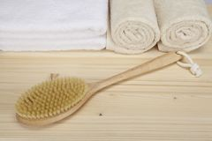 Bath brush and towels on a tabletop of spruce wood Royalty Free Stock Photo