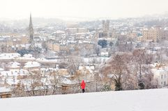 Bath City in the Snow. Person in a red jacket looking at the City of Bath from a snow covered hill Stock Image