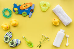 Bath cosmetic set for kids, towel and toys yellow background top view space for text Royalty Free Stock Image