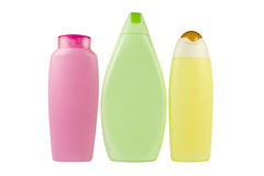 Bath cosmetics. A detail of three shampoo and body lotion bottles - yellow, pink and green with copy space, isolated on white Stock Photography
