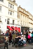 City building scene. BATH, ENGLAND - OCT, 18: Local and domestic tourist atmosphere scene sit and relax at public bench among old roman city atmosphere stock photography