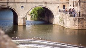 Pulteney Bridge and River Avon. Bath, England. 4th July, 2015: people by the  Pulteney Bridge and River Avon in  Bath Somerset England UK Royalty Free Stock Photography