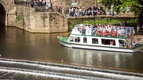 The Weir and boats. Bath, England. 4th July, 2015:  The Weir and boat full of tourist in  River Avon,  Bath Somerset England UK Stock Photography