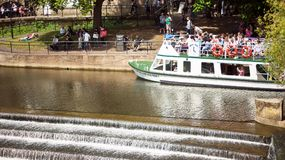 Tourist boat in River Avon. Bath, England. 4th July, 2015:  The Weir and boat full of tourist in  River Avon,  Bath Somerset England UK Royalty Free Stock Image