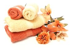 Bath Ensemble. Beautiful bath ensemble with wash cloths and towels in burnt orange and sand colors on white Royalty Free Stock Images