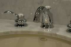 Bath Fixtures. Chrome and white bathroom fixtures on a white marble sink Royalty Free Stock Photo