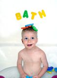 Bath and Fun. Bath time can be fun especially if you have big blue eyes and a sheepish grin. Colorful foam letters spell bath and sit on top of little boys head stock photos