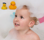 Bath girl with soap suds. Adorable bath baby girl with soap suds on hair in the bathroom Royalty Free Stock Images