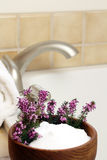 Bath Heather. Epsom salts with purple heather flowers in a teak bowl make for a relaxing time Stock Image