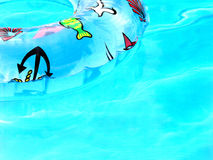 Blue color of holidays. Detail of the turquoise water and inflatable swimming trainer stock photo