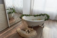 Bath on lion`s paws, decorated with flowers. On the floor are candles.A romantic setting for a date. Bath on lion`s paws, decorated with flowers. On the floor Stock Photo