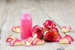 Bath oil and pink roses Stock Photos