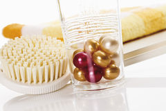 Bath pearls in glass, brush and towel in background Royalty Free Stock Photography