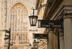 Bath Pump rooms and Abbey. Bath Pump rooms exterior signs and columns with the west window of Bath Abbey in the background Stock Photos
