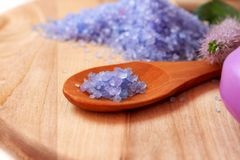 Bath salt. Purple bath salt placed in a wooden spoon, body care treatment stock image
