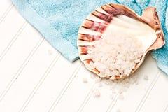 Bath salt. Beach towel with seashell and bath salt on a white beadboard Stock Photos