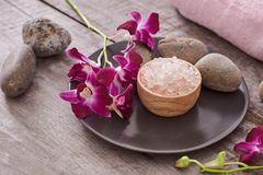 Bath salt at bamboo bowl and orchids flowers on dark wood stock images