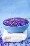 Bath salt, lavander and towel. Violet bath salt and twigs of lavender in blue bowl and white towel on blue linen cloth Stock Image