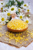 Bath salt on wooden spoon. With chamomile on mat, shallow focus Royalty Free Stock Photos