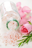 Bath salts. Pink bath salts in a glass jar with flowers and herbs Royalty Free Stock Images