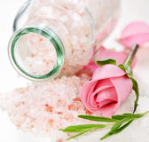 Bath salts. Pink bath salts in a glass jar with flowers and herbs Stock Photography