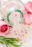 Bath salts. Pink bath salts in a glass jar with flowers and herbs Stock Images