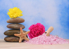 Bath Salts. Pink Bath Salts and Massage Stones on Blue Textured Background Royalty Free Stock Photos