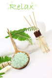 Bath Salts and Essential Oils. Green bath salts in a wooden spoon with essential oils and white towel. Extreme shallow DOF with selective focus on bath salts Stock Photography
