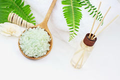 Bath Salts and Essential Oils. Green bath salts in a wooden spoon with essential oils and white towel. Extreme shallow DOF with selective focus on bath salts Royalty Free Stock Photography