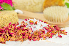Bath salts and rose petals. Bath salts covered in fragrant dried rose petals or floral potpourri with a bathing brush and sponge for pampering yourself at bath Royalty Free Stock Image
