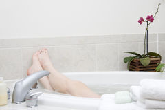 Bath series. Feet II. Bathtime. Girl's feet sticking out from the bath tub Royalty Free Stock Photos