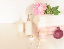 Bath setting in white and pink colors. Towel, aroma oil, flowers, soap. Selective focus, horizontal. Bath settingin white and pink colors. Towel, aroma oil Stock Photo