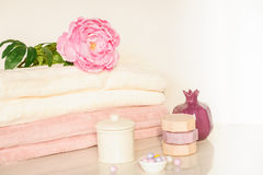 Bath setting in white and pink colors. Towel, aroma oil, flowers, soap. Selective focus, horizontal. Bath settingin white and pink colors. Towel, aroma oil Royalty Free Stock Images