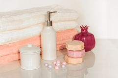 Bath setting in white and pink colors. Towel, aroma oil, flowers, soap. Selective focus, horizontal. Bath settingin white and pink colors. Towel, aroma oil Royalty Free Stock Photo