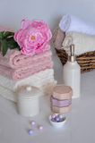 Bath setting in white and pink colors. Towel, aroma oil, flowers, soap. Selective focus, horizontal. Bath settingin white and pink colors. Towel, aroma oil Royalty Free Stock Photography