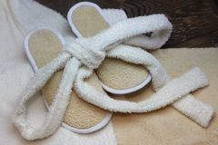 Bath slippers and bathrobe. On wooden boards stock photos