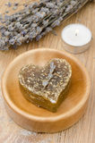 Bath soap with lavender in a heart and a candle on a wooden tabl Stock Image