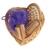 Bath spa kit. Bath anti-cellulitis spa massage kit with comb, brush, sponge and hairbrush in heart shape basket isolated on white background stock image