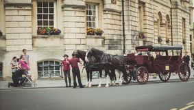 Carriage in Bath. Bath Spa,UK-July 4,  2015: Two horses ready to pull a carriage full of tourists around the beautiful city of Bath on a sunny day. This is  a Royalty Free Stock Photo