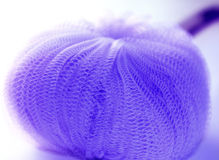 Bath Sponge. Purple bath sponge slight blur on off white background Royalty Free Stock Images
