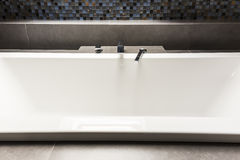Bath with steely tap. White bath in modern bathroom with shiny tiles Stock Photo