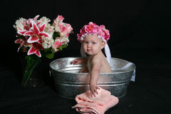 Bath Time. Little baby girl sitting in bath basin playing with towels and flowers with a cap on her head Royalty Free Stock Photo