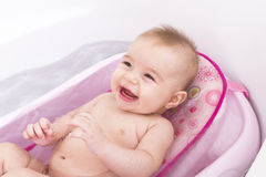 Bath Time. Pretty smiley baby girl is having a bath in her bathtub Royalty Free Stock Images