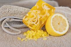 Bath time. Loofah sponge, natural soap, bath salt and lemon stock photos